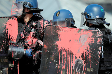 French gendarmes are covered with paint as protestors clash with police forces during a demonstration on Act 44 (the 44th consecutive national protest on Saturday) of the yellow vests movement in Nantes