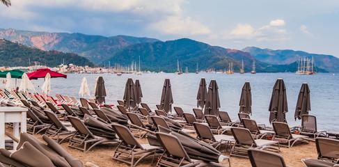 deck chairs under umbrella on resort beach sea view
