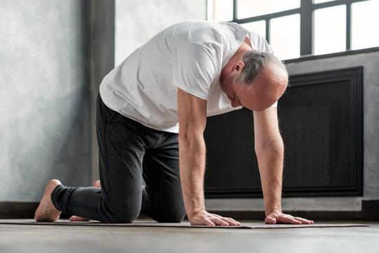 Senior bald yogi men practices yoga asana marjariasana or cat-cow pose at home