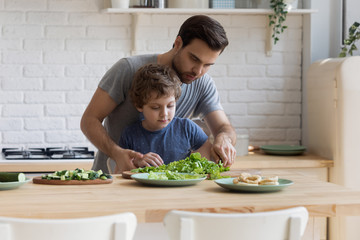 Young father teaching little focused school kid son slicing vegetables.
