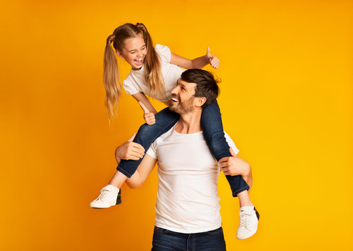 Father Giving His Daughter Piggyback Ride Gesturing Thumbs-Up In Studio