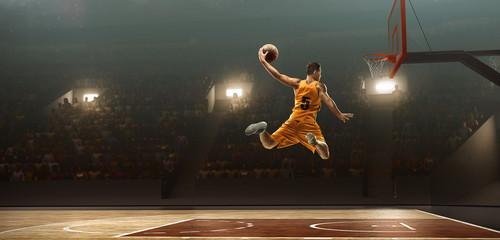 Basketball player on basketball court in action. Slam dunk. Jump shot