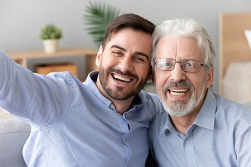 Happy old father young son take selfie, mobile camera view
