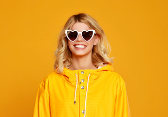 happy emotional girl with sunglasses on autumn colored yellow background.