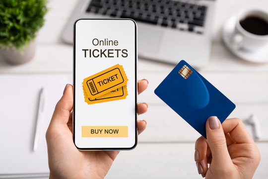 Woman holding smartphone with online tickets app and credit card