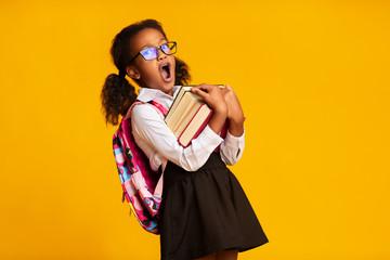 Sleepy African American Schoolgirl Yawning Carrying Books, Yellow Background