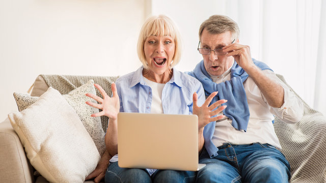 Surprised mature couple winning online auction, using laptop