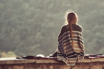 Young woman enjoying nature sitting on top of a hill. Back view