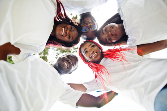 Group of happy african volunteers hugs in park. Africa volunteering, charity, people and ecology concept. Look from down.