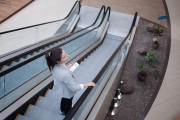 Young businesswoman on the escalator and a phone in her hands. In the office or business center.