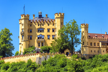 Fototapete - Hohenschwangau Castle near Fussen, Bavaria, Germany. Schloss Hohenschwangau is a landmark of German Alps. Scenic view of famous castle in summer. Palace of king Ludwig II in Schwangau village.