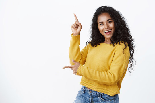 Cheerful carefree african-american woman in yellow sweater with curly haircut, smiling and laughing joyfully dancing as pointing sideways, showing left and up copy space, white background