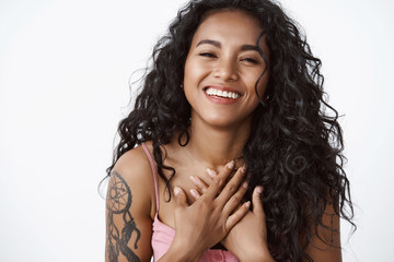 Attractive modern curly-haired african american woman with tattoos, hold hands on chest grateful and touched, laughing and smiling, enjoying touching lovely date, white background