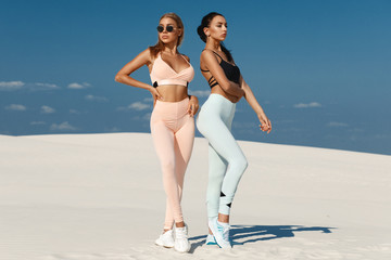 Beautiful fitness models in sportswear. Couple athletic girls in leggings outdoor
