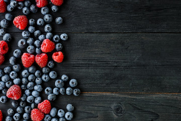 Various fresh summer berries. Mix of fruits and berries on black background. Fruit banner. Top view, overhead