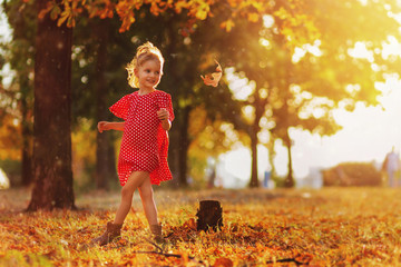 Journey in nature. Adorable happy girl throwing the fallen leaves up, playing in the autumn park. Little blonde hair and blue eyes girl smiling expression. Girl in polka dot red dress and boots