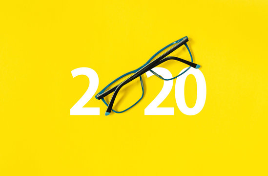 happy new year 2020. 2020 with glasses on yellow isolated background