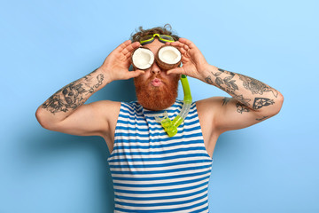 Photo of handsome bearded man keeps coconuts on eyes, looks curiously into distance, wants to see something over sea horizon, wears snorkeling mask and striped vest, spends summer holiday at sea