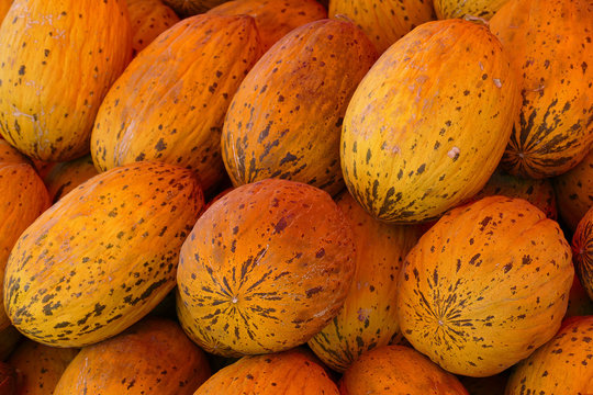 melons stacked in an area for sale, a large amount of melons for sale,