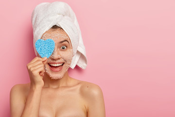 Horizontal shot of happy young female model covers eye with cosmetic sponge, cleans face by natural white sea salt scrub mask, visits spa salon, has sooth healthy skin, naked body, models indoor
