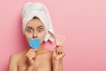 Headshot of surprised young lady with bugged eyes, wears white towel on wet head, holds two heart shaped sponges, poses over pink wall, reduces acnes with natural facial mask, shocked to have pimple