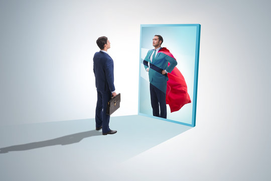 Businessman seeing himself in mirror as superhero