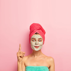 Foto op Aluminium Spa Beauty and spa concept. Photo of lovely woman points index finger above, wears nourising mask, reduces pimples, avoids problems of skin dryness, wrapped in bath towel, isolated on pink wall.