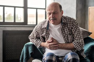 Obraz Senior hispanic man is having pancreatitis or gastritis or colitis sitting alone at the living room. Poor health at old age concept - fototapety do salonu