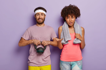 Photo of puzzled man holds weight, dressed in t shirt and white headband, his ethnic curly woman stands near, has towel around neck for wiping sweat, have workout together in fitness center.