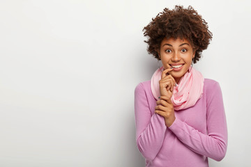 Studio shot of happy Afro woman with curly hairstyle, touches index finger on lips, has toothy smile, dressed casually, looks straightly at camera, stands against white background, copy space for text