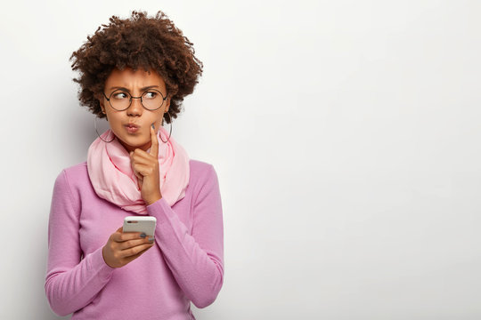 Pensive dark skinned woman looks thoughtfully aside, holds mobile phone, waits for call, purses lips, has Afro haircut, dressed in violet jumper with scarf, keeps index finger on cheek, poses indoor