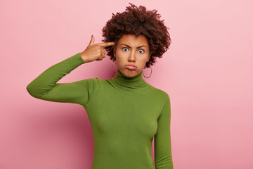 Frustrated dark skinned woman makes suicide gesture, keeps index finger on temple, tilts head, sighs from tiredness, wears casual green turtleneck, looks with unhappy expression, isolated on pink wall