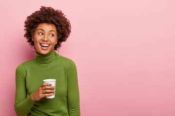 Image of lovely dark skinned curly woman holds takeaway coffee, enjoys break, wears green poloneck jumper, looks on right side, poses against pink wall, free space for your advertising content