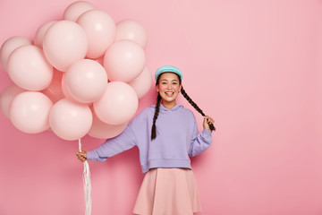 Pretty cheerful Asian teenage girl comes on holiday with bunch of airballoons, has two dark long plaits, rouge cheeks and minimal makeup, wears oversized purple jumper and skirt, being in good mood