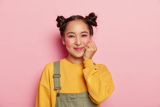 Beautiful brunette woman with two hair buns, smiles positively, enjoys pleasant talk, keeps hand near face, has minimal makeup, wears casual outfit, poses against pink background. Asian beauty concept