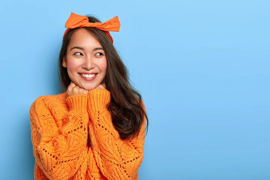 Studio shot of happy upbeat woman wears bright orange knitted jumper, bow headband, holds hands under chin, glad to hear heartwarming words from stranger, rejoices having nice unforgettable day