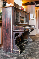 A very old upright acustic piano on a wooden floor, perspective view.