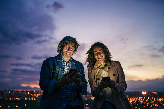 a senior man and young woman using a smartphone with a city background at night