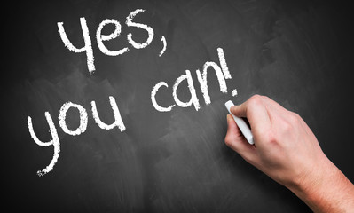 """hand writing """"yes, you can!"""" on a blackboard"""
