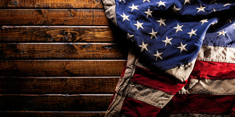 Old and worn American flag on dark wooden background