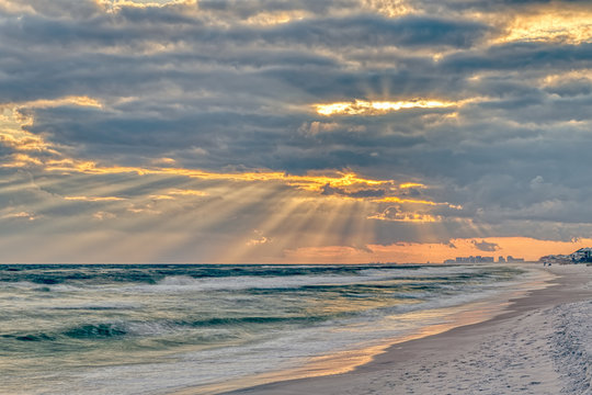 Dramatic pastel light sunset with sun rays in Santa Rosa Beach, Florida with Pensacola coastline coast cityscape skyline in panhandle and ocean