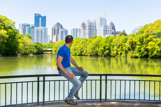 Young man sitting on railing in Piedmont Park in Atlanta, Georgia looking at scenic cityscape skyline urban view with city skyscrapers downtown by Lake Clara Meer