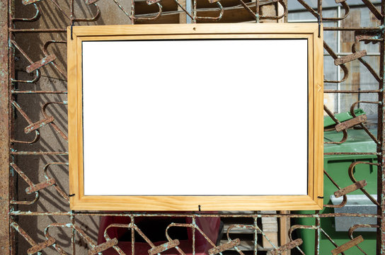 Blank white mock up template/background texture of an information/notice board hanging on a rustic iron gate with wooden frame.