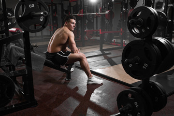 Athlete professional athlete rests before exercise on bench in gym