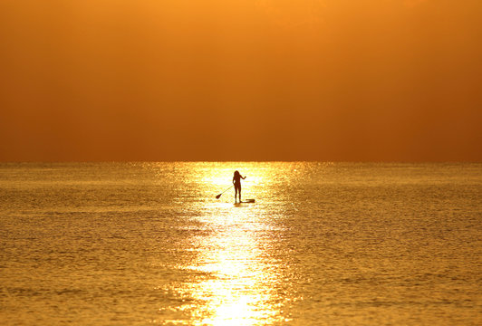 A woman paddles on a stand-up board during sunrise in a beach in Larnaca