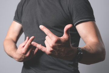 Man is showing it is rocks gesture isolated on a gray background.