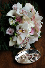 Wedding still life of rings and bride's bouquet.