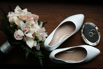 Wedding still life of flowers rings and shoes bride.