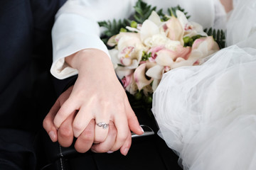 Hands of the bride and groom on the wedding day.