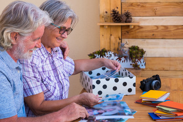 An elderly couple with gray hair looks into the box of family photographs and smiles. Concept of memories and real life